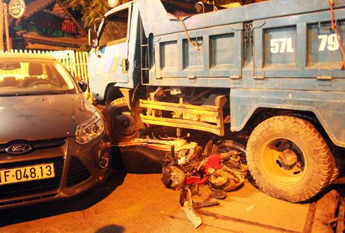Chiếc xe máy của gia đình 3 người bị cuốn vào gầm, biến dạng. Ảnh: An Nhơn