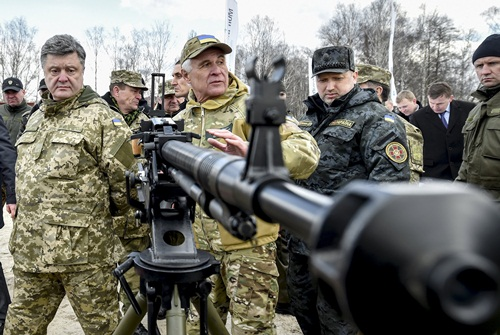 Ukraine's President Petro Poroshenko (L) and Ukrainian secretary to the National Security and Defence Council Oleksandr Turchynov (3rd L) inspect weapons and military equipment as they visit the training center of the Ukrainian National Guard outside Kiev April 4, 2015. REUTERS/Mykola Lazarenko/Ukrainian Presidential Press Service/Handout via Reuters ATTENTION EDITORS - THIS PICTURE WAS PROVIDED BY A THIRD PARTY. REUTERS IS UNABLE TO INDEPENDENTLY VERIFY THE AUTHENTICITY, CONTENT, LOCATION OR DATE OF THIS IMAGE. FOR EDITORIAL USE ONLY. NOT FOR SALE FOR MARKETING OR ADVERTISING CAMPAIGNS. THIS PICTURE IS DISTRIBUTED EXACTLY AS RECEIVED BY REUTERS, AS A SERVICE TO CLIENTS