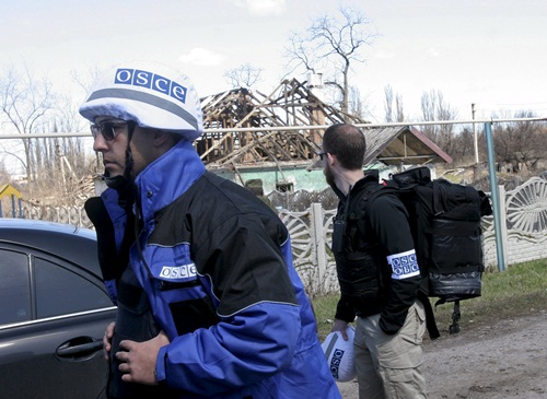 Members of the Special Monitoring Mission of the Organization for Security and Cooperation (OSCE) to Ukraine walk past a house damaged by shelling, in the village of Spartak outside Donetsk April 10, 2015. Ukraine's military and pro-Russian rebels accused each other on Friday of intensifying attacks in separatist eastern territories despite a two-month-old ceasefire deal. REUTERS/Igor Tkachenko