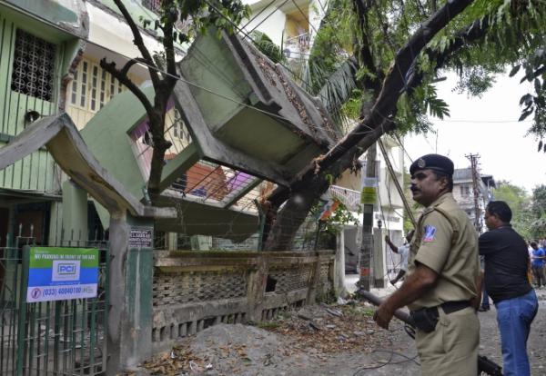 Một nhân viên an ninh đứng trước ngôi nhà sập ởSiliguri, Ấn Độ. Ảnh: Reuters