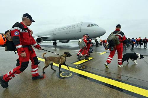 Lực lượng cứu hộ Hà Lan và chó nghiệp vụ rời sân bayEindhoven đến Nepal. Ảnh: AFP