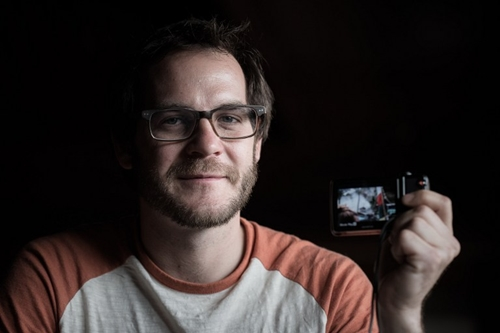 In this photograph taken on May 3, 2015, US trekker Corey Ascolani, 34, holds the camera he used record a video of the earthquake during an interview in Kathmandu. Ascolani was among hundreds of tourists travelling in the scenic Langtang region when a 7.8-magnitude earthquake on April 25 flattened villages and unleashed avalanches in Nepal's Himalayas, killing more than 7,300 people. AFP PHOTO/Philippe Lopez
