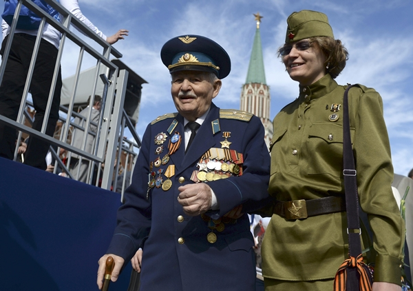 A World War Two veteran (L) arrives to watch the Victory Day parade at Red Square in Moscow, Russia, May 9, 2015. Russia marks the 70th anniversary of the end of World War Two in Europe on Saturday with a military parade, showcasing new military hardware at a time when relations with the West have hit lows not seen since the Cold War. Many Western leaders have boycotted the celebrations over the crisis in Ukraine, making Chinese President Xi Jinping Moscow's most high profile guest. REUTERS/Host Photo Agency/RIA Novosti ATTENTION EDITORS - THIS IMAGE HAS BEEN SUPPLIED BY A THIRD PARTY. IT IS DISTRIBUTED, EXACTLY AS RECEIVED BY REUTERS, AS A SERVICE TO CLIENTS