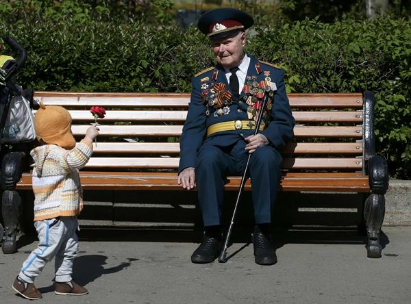 A little girl gives a flower to a blind World War Two veteran during the Victory Day celebrations at Gorky park in Moscow, Russia, May 9, 2015. Russia marks the 70th anniversary of the end of World War Two in Europe on Saturday with a military parade, showcasing new military hardware at a time when relations with the West have hit lows not seen since the Cold War. REUTERS/Maxim Zmeyev