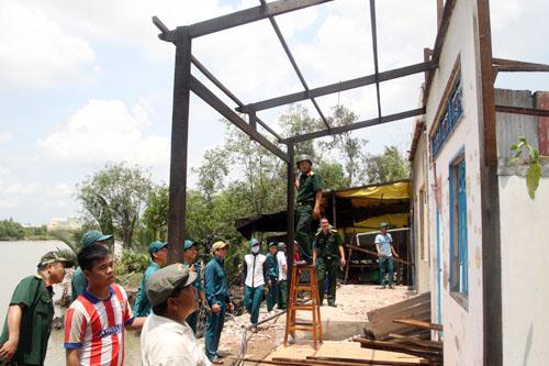 Lực lượng Ban chỉ huy quân sự huyện Nhà Bè giúp dân di dời nhà cửa. Ảnh: An Nhơn
