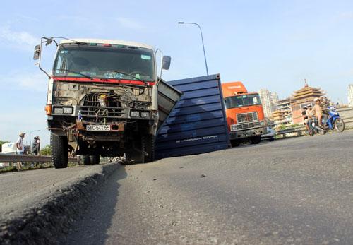 Thùng container bị rơi xuống đường khi bánh xe đầu kéo mất thăng bằng vì lọt xuống rãnh.