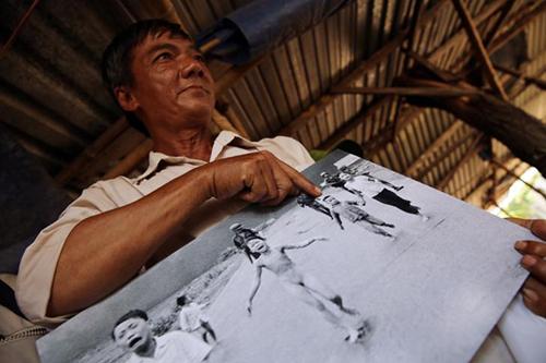 Ông Ho Van Bon chỉ vào bức ảnh chụp cô Phúc và là cậu bé bên trai cô trong bức ảnh năm 1972. Ảnh: AP