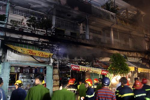 Đám cháy đã thiêu rụi toàn bộ cửa hàng và làm những căn phía trên ám khói đen. Ảnh: An Nhơn