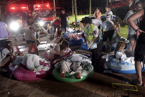 Injured victims from an accidental explosion during a music concert lie on the ground at the Formosa Water Park in New Taipei City, Taiwan, June 27, 2015. About 200 people were injured after a fire suspected to have stemmed from the explosion of an unknown flammable powder occurred in a recreational park in northern Taiwan, local media reported on Saturday. REUTERS/Wang Wei TAIWAN OUT. NO COMMERCIAL OR EDITORIAL SALES IN TAIWAN. TPX IMAGES OF THE DAY