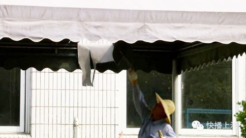 Một công nhân kiểm tra lỗ hổng trên mái do tấm kim loại từ máy bay của Air France rơi trúng. Ảnh: Shanghai Daily