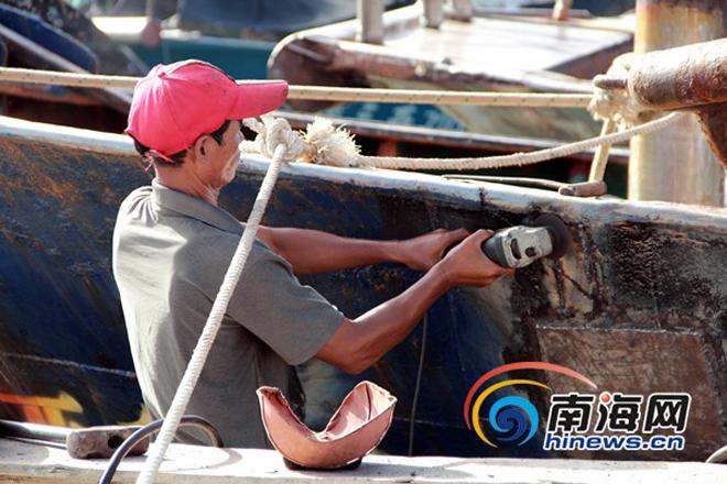 Một ngư dân sửa lại mạn tàu ở cảng Tam Á. Ảnh: HiNews
