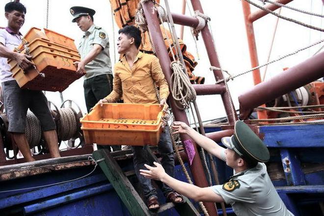 Trong quá trình chuẩn bị, ngư dân Trung Quốc còn nhận được sự hỗ trợ của quân đội, biên phòng. Lính biên phòng Trung Quốc cùng ngư dân chuyển ngư cụ lên tàu hôm 28/7, tại cảng cá huyện Lâm Cao, cách thành phố Hải Khẩu, Hải Nam, khoảng 50 km về phía tây. Ảnh: Ifeng