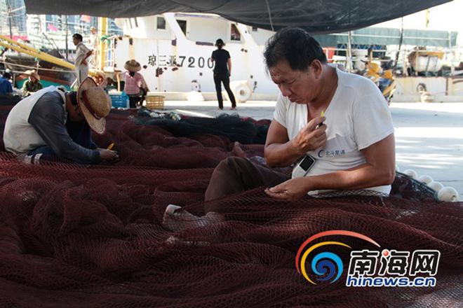 Một ngư dân khác vá lại lưới đánh bắt. Ảnh: HiNews