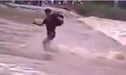 Thanh niên trượt ngã khi liều mạng chạy qua dòng nước lũ