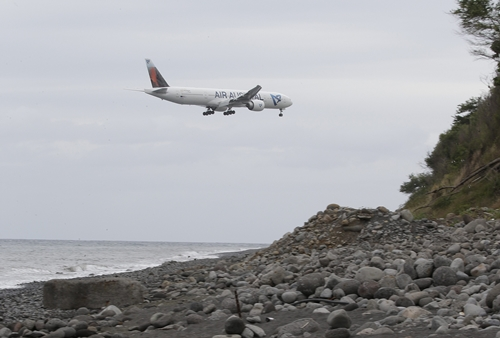 An airplane flies over the Jamaique beach in Saint-Denis on the French Indian Ocean island of La Reunion, August 3, 2015. On Sunday, a small piece of metal debris found washed up on a beach on Reunion was taken into police custody. A flaperon, which help pilots control an aircraft in flight, will be analysed at a lab near Toulouse staffed by experts that is operated by the French defence ministry to determine if the plane debris found on Reunion Island came from Malaysia Airlines Flight MH370 which disappeared without a trace 16 months ago with 239 passengers and crew on board. REUTERS/Jacky Naegelen