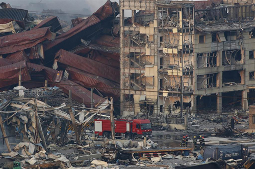 [Caption]iremen work among several destroyed buildings and containers after a huge explosion rocked the port city of Tianjin, China