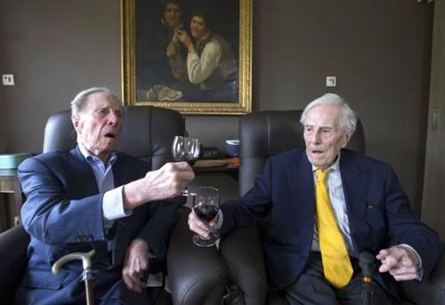 Cặp song sinhPaulus (trái) vàPieter Langerock nâng ly rượu vang tại viện dưỡng lão ở Bỉ. Ảnh: Reuters
