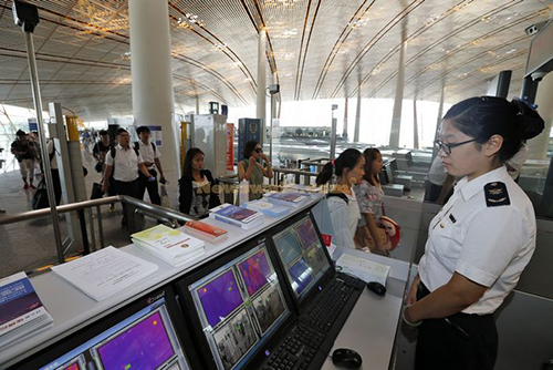 [Caption]A quarantine staff member monitored body temperatures of passengers who passed infrared thermometry machine at Beijing Capital International Airport in Beijing, capital of China, Aug. 14, 2014. To prevent the deadly Ebol