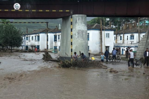 Residents attempt to clear flood debris from under a bridge in the city of Rajin in North Korea in this August 22, 2015 picture taken by a recent visitor.