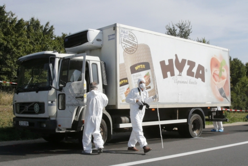 Forensic police officers inspect a parked truck in which up to 50 migrants were found dead, on a motorway near Parndorf, Austria August 27, 2015.