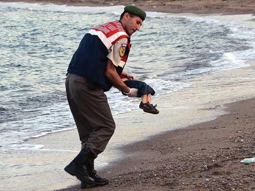 Nhân viên cảnh sát bế thi thể bé Aylan lên bờ. Ảnh: AP.