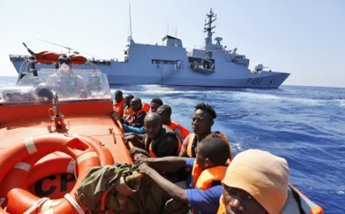 Migrants sit on a Norwegian Coast Guard boat after being transferred from the Italian Navy Ship Fulgosi during a migrant search and rescue mission off the Libyan Coast. Photo: AP