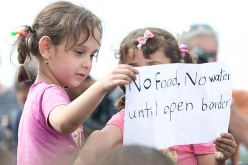 """Hai em bé cầm tờ giấy có dòng chữ""""Không ăn, uống cho tới khi mở cửa biên giới"""". Ảnh: Mirror"""