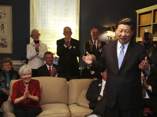 [Caption]a's Vice President Xi Jinping speaks at the home of Roger and Sarah Lande (2nd L) in Muscatine, Iowa February 15, 2012. Xi joked about receiving a gift of popcorn during his first visit to Muscatine in 1985.