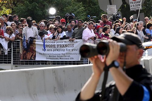 [Caption]People stand behind a security barrier asPopeFrancis arrives at theVatican Embassy in WashingtonSeptember 22, 2015