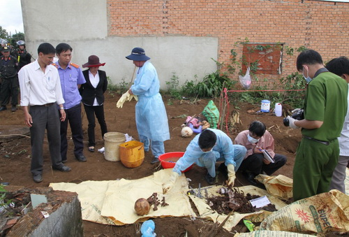 Lực lượng chức năng khám nghiệm tử thi sau khi khai quật. Ảnh: Hoài Thanh