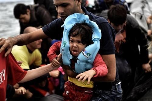 1. Người đàn ông đang bế một đứa trẻ trong nhóm người tị nạn khi cập bến đảo Lesbos của Hy Lạp, sau hành trình vượt biển Aegean, Thổ Nhĩ Kỳ, hôm 30/9. Ảnh: AFP