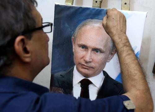 Iraqi artist Mohammed Karim Nihaya touches up a painting of Russian President Vladimir Putin in his studio in the Karada district of Baghdad on October 7, 2015 (AFP Photo/Sabah Arar)