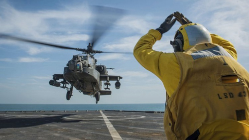 [Caption]A Boeing AH-64 Apache helicopter from the US Army 4-501st Attack Reconnaissance Battalion undergoes deck landing qualifications on 24 February 2015 in the Persian Gulf on amphibious dock landing ship USS Fort McHenry (LSD 43), serving as part of Iwo Jima Amphibious Ready Group and deployed in support of US 5th Fleet. Source: US Navy / Mass Communication Specialist 3rd Class Adam Austin