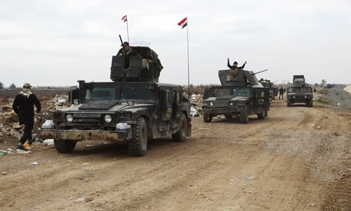 Iraqi security forces ride on military vehicles as they advance towards the center of Ramadi city, Iraq