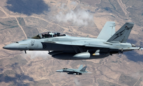 Two Australian F/A-18 Hornets fly in formation over Iraq. The government is considering extending military operations against Islamic State into Syria. Photograph: SGT Pete/Australian Government, Department of Defence