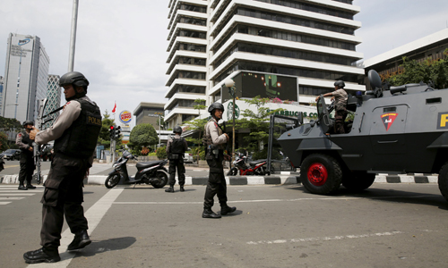[Caption]policemen with weapons and an armoured vehicle guard in front of a Starbuck cafe at Thamrin business district in Jakarta, January 14, 2016