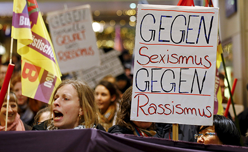 "[Caption]Women shout slogans and hold up a placard that reads ""Against Sexism - Against Racism"" as they march through the main railway station of Cologne, Germany, January 5, 2016."