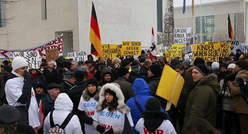 [Caption]Người biểu tình mang theo các biểu ngữ phản đối, tập trung bên ngoài dinh Thủ tướng Đức Angela Merkel hồi cuối tuần trước. Ảnh:BBC