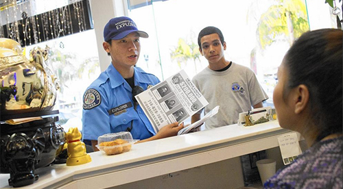 [Caption]Police Explorers Kevin Nguyen, left, and Christopher Cervantes, right, hand out fliers of the three inmates who escaped from an Orange County jail to businesses near Asian Garden Mall in Westminster in late January. (Kevin Chang / Weekend)