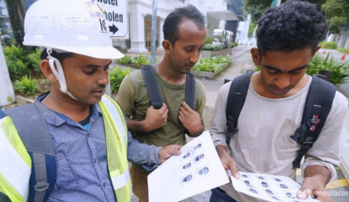 Construction workers looking at the mug shots of 27 Bangladeshi foreign workers who were arrested here under the Internal Security Act. (Photo: Ernest Chua/TODAY)