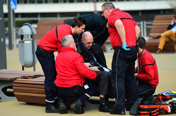 [Caption]A victim receives first aid by rescuers near Maalbeek metro station. Photograph: Emmanuel Dunand/AFP/Getty Images