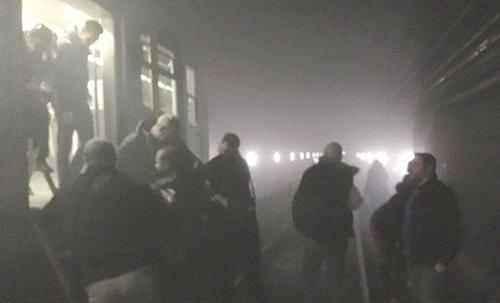 [Caption]Evacuated passengers walk though the smoke-filled tunnels
