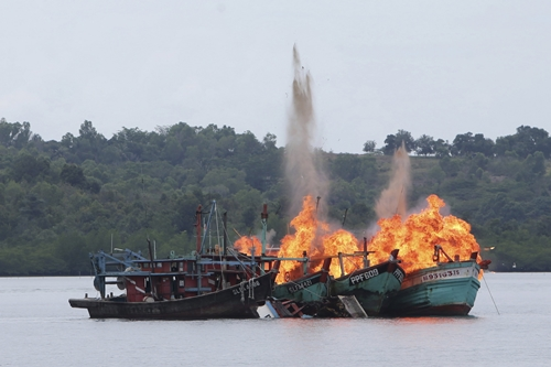 Malaysian and Vietnamese fishing boats are destroyed for illegal fishing by the Ministry of Maritime Affairs and Fisheries, police and navy, in Batam, Riau Islands, Indonesia April 5, 2016 in this photo taken by Antara Foto. The Indonesian government reportedly sank 28 illegal foreign fishing boats simultaneously in nine locations across the country. REUTERS/M N Kanwa /Antara Foto ATTENTION EDITORS - THIS IMAGE HAS BEEN SUPPLIED BY A THIRD PARTY. IT IS DISTRIBUTED, EXACTLY AS RECEIVED BY REUTERS, AS A SERVICE TO CLIENTS. FOR EDITORIAL USE ONLY. NOT FOR SALE FOR MARKETING OR ADVERTISING CAMPAIGNS. MANDATORY CREDIT. INDONESIA OUT. NO COMMERCIAL OR EDITORIAL SALES IN INDONESIA.