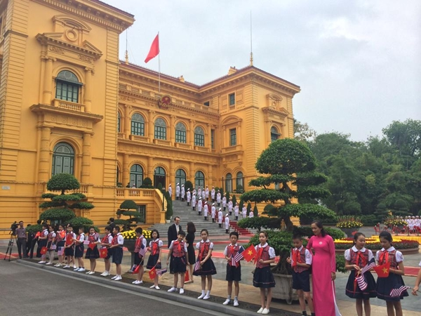 Các em học sinh cầm cờ hoa sẵn sàng chào đón Tổng thống Mỹ Barack Obama. Ảnh: Việt Anh.