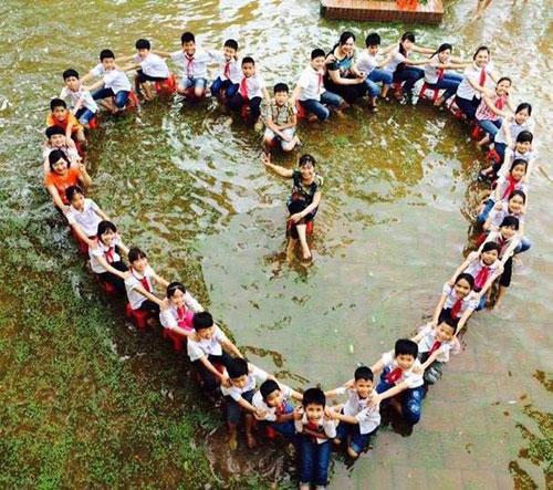 Học sinh xếp hình trái tim chụp ảnh kỷ yếu giữa sân trường ngập nước 1