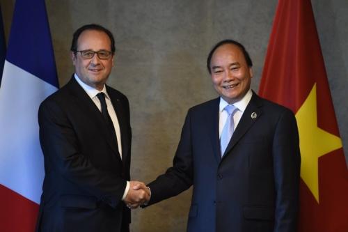 Thủ tướng Nguyễn Xuân Phúc bắt tay với Tổng thống Pháp Francois Hollande. Ảnh: AFP