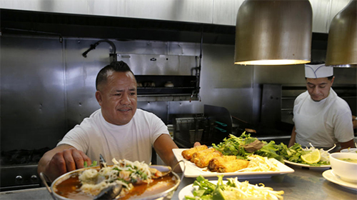 Los Angeles TimesChef Juan Ramirez, left, and Omar Reynoso, right, prepare meals at hotspot Song Long. Despite their political differences  the Vietnamese tend to be Republican, and the Latinos Democratic  experts say they come together to solve a labor shortage facing the area.