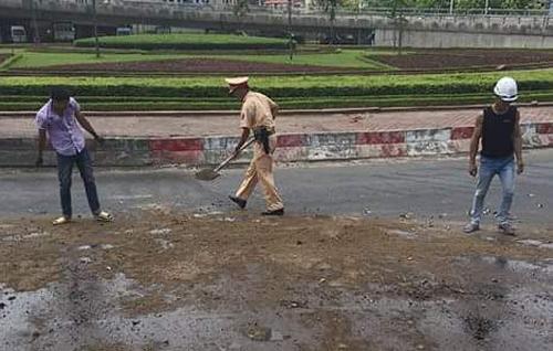 Cảnh sát đổ cát dọn vết dầu loang trên đường