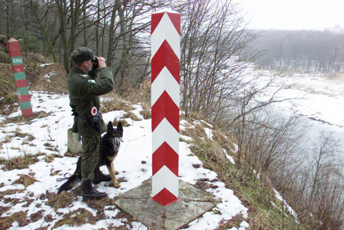 A Polish border guard and his dog overlook the Polish-Russian border near the village of Ostre Bardo, February 1, 2001.PETER ANDREWS/REUTERS