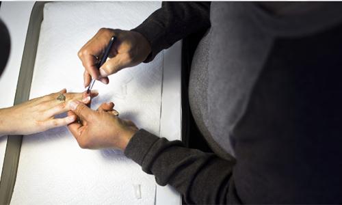 Một thợ gốc Việt đanglàm móng cho khách hàng ở tiệm nail tại bang California, Mỹ. Ảnh minh họa: KPCC